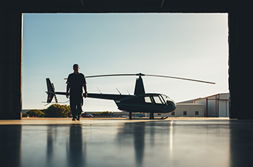 Silhouette of helicopter with a pilot in the airplane hangar